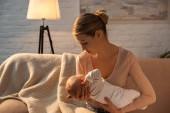 krásná mladá matka držení dítěte při kojení v noci