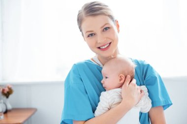 happy young mother holding newborn baby and smiling at camera in hospital room