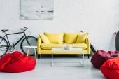 Fotografie geräumiges möbliertes Wohnzimmer mit gemütlichen Sitzsäcken und bequemem gelben Sofa