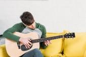 mladý muž sedí na žluté pohovce a hrál na akustickou kytaru