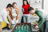 Fényképek multikulturális, barátok, szórakozás, férfiak játszani asztali foci közben lányok watching játék