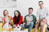 Fotografie laughing multicultural friends with funny nickname labels on foreheads sitting on yellow sofa