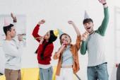 Veselá mnohonárodnostní přátel v vícebarevné papírové čepice baví doma párty