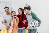 Veselá mnohonárodnostní přátelé v vícebarevné papírové čepice baví doma party a zpěv karaoke