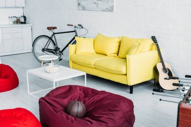 spacious furnished living room with beanbag chairs, sofa and coffee table