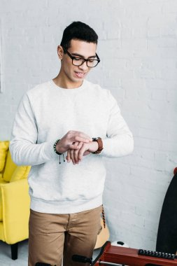 handsome mixed race man in white sweatshirt checking time on wristwatch