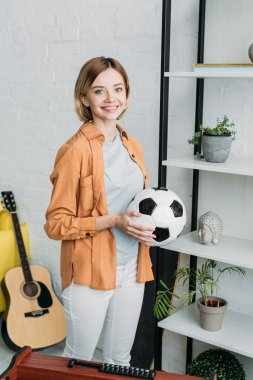 smiling pretty girl in orange shirt and white jeans holding soccer ball