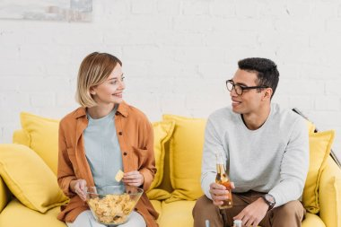 interracial couple talking and enjoying snacks and drinks while sitting on yellow sofa