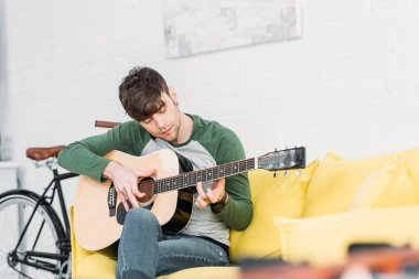 handsome young man playing acoustic guitar while sitting on yellow sofa