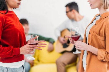multicultural girls holding wine glasses and talking, men sitting on yellow sofa on background
