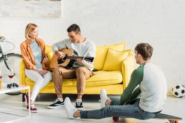 smiling mixed race man playing guitar for multicultural friends at home