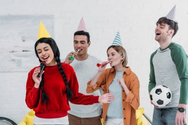 multicultural friends in colorful paper hats singing karaoke at home party
