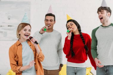 multiethnic multicultural friends in colorful paper hats having fun at home party while singing karaoke