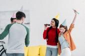 Veselá multikulturní přátel v barevné papírové čepice doma zpívá karaoke párty
