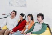 mnohonárodnostní přátel poslech hudby se sluchátky při posezení na žluté pohovce v obývacím pokoji