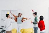multikulturní přátel baví doma párty při karaoke, chozeni v obývacím pokoji