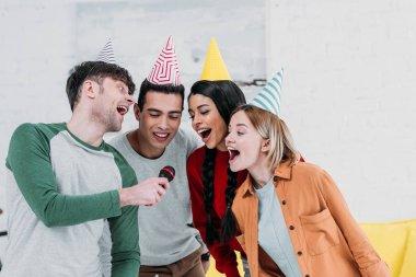 multiethnic having fun at home party while singing karaoke