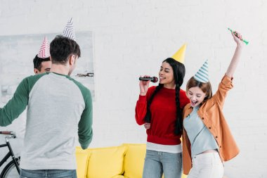 cheerful multicultural friends in colorful paper hats singing karaoke at home party