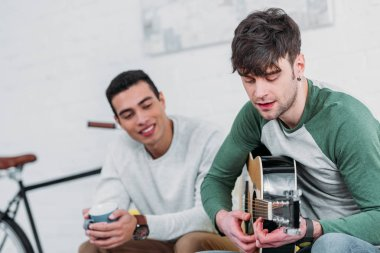handsome young man playing guitar to mixed race friend