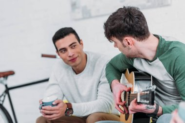 young handsome man playing guitar to mixed race friend