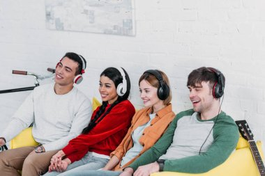 multiethnic friends listening music with headphones while sitting on yellow sofa in living room