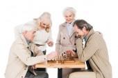 Fotografie bývalý přáteli, kteří hrají šachy u starší ženy, izolované na bílém
