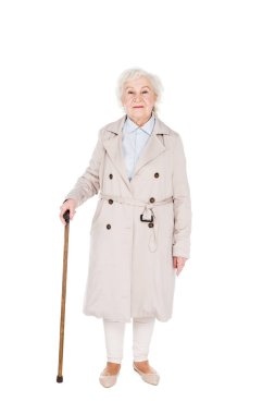cheerful senior woman standing with walking cane isolated on white