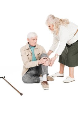 senior man holding knee while having arthritis pain near caring wife isolated on white