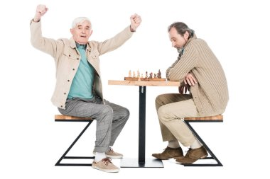 cheerful retired man celebrating victory after playing chess with friend isolated on white