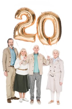cheerful retired people holding balloons isolated on white