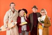 Fotografia Uomo pensionato allegro che tiene il pattino vicino la donna parla al telefono e gli amici con i fiori isolati su orange