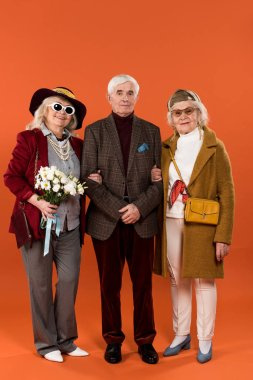 stylish senior women standing between retired man and holding flowers on orange background