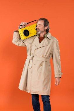 trendy senior man holding yellow boombox isolated on orange
