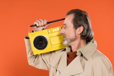 cheerful retired man looking at yellow boombox isolated on orange