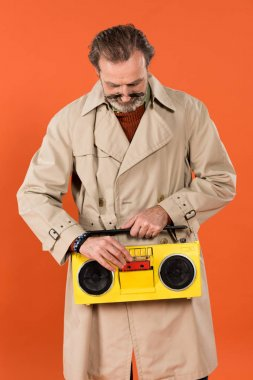 cheerful retired man pressing button yellow boombox isolated on orange