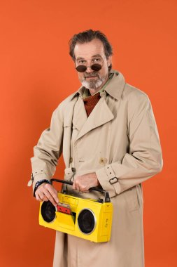 stylish retired man holding yellow boombox in hands isolated on orange