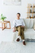 Photo thoughtful senior man sitting on sofa in modern living room
