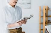 vista potata delluomo maggiore in piedi e leggendo il libro a casa