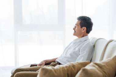 thoughtful senior man sitting on sofa at home