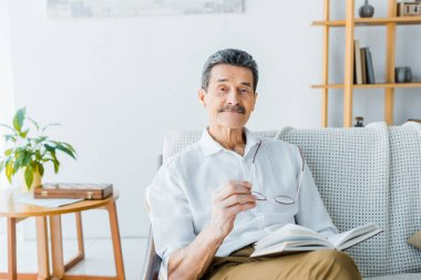 happy senior man holding book and glasses at home