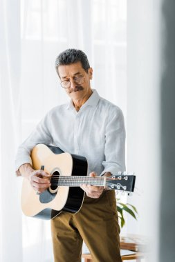 senior man in glasses playing acoustic guitar at home
