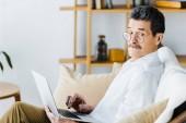 Fotografie Älterer Mann mit Laptop auf Sofa überrascht