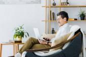 Fotografie Senior woman in Gläsern mit Laptop sitzend auf sofa