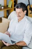 pensionierter Mann in Gläsern mit Laptop sitzend auf sofa