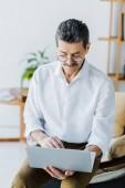 Rentner mit Schnurrbart und Brille sitzt mit Laptop auf Sofa