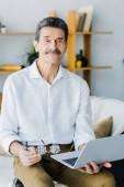 Fotografie fröhlichen Rentner mit Schnurrbart mit Laptop zu Hause