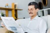 uomo maggiore allegro in occhiali da lettura giornale di viaggio stando seduti sul divano
