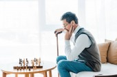 Fotografie thoughtful pensioner in glasses looking at chess board and holding walking stick