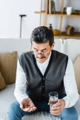 Fotografie retired man looking at pills while holding glass of water at home