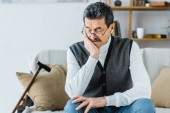retired man sitting near walking stick with closed eyes